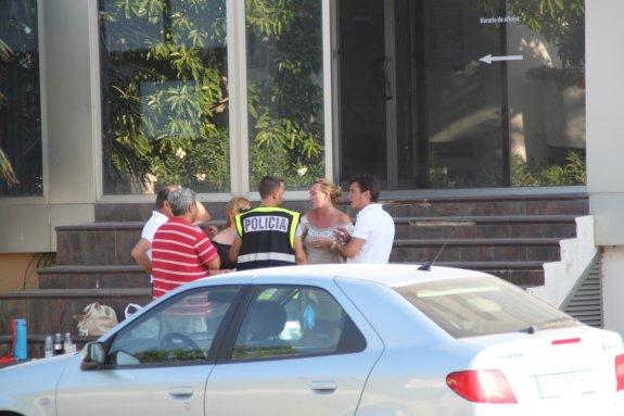 Un agente de la Policía Nacional habla con varias personas que se encontraban en la urbanización.