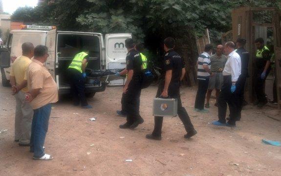 Dos empleados del retén fúnebre introducen el cadáver del anciano en el furgón.