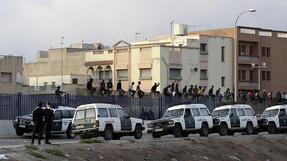 Inmigrantes encaramados en la parte alta de la valla de Melilla.