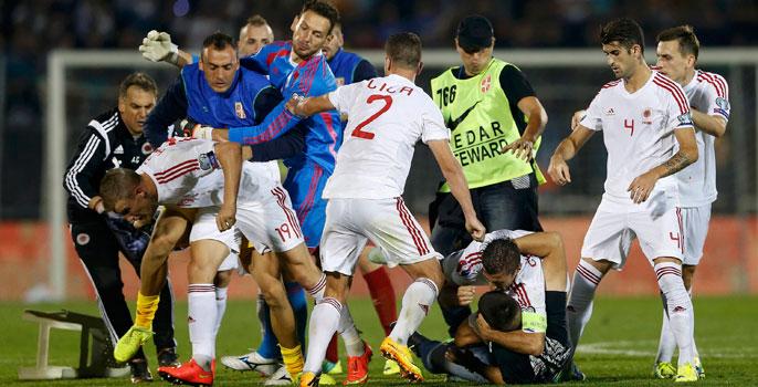 Varios jugadores de Albania y Serbia se pelean sobre el césped.