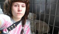 Imagen de la joven junto a la jaula en la que se mantiene encerrada a su perra
