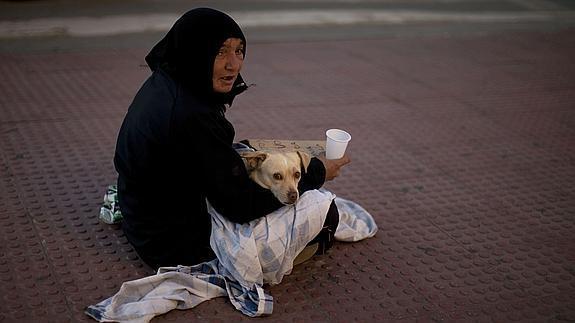 Mujer, junto a su perro, pide limosna en una calle de Málaga