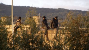 Una treintena de subsaharianos permanecen encaramados en lo alto de la verja.