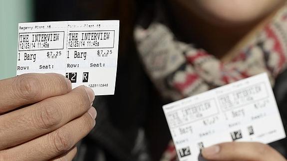 Un hombre enseña unas entradas para el estreno de la película.