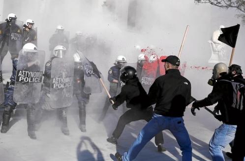 Manifestantes antisistema griegos luchan con la policía antidisturbios durante una protesta