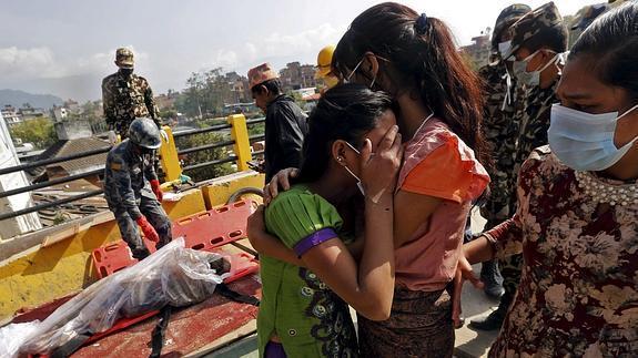 Dos mujeres lloran desconsoladas ante el cadáver de un familiar.