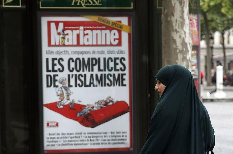 Una musulmana se detiene en los campos Elíseos, en París, frente a un afiche de la portada de la revista Marianne que contiene un reportaje sobre el islamismo.