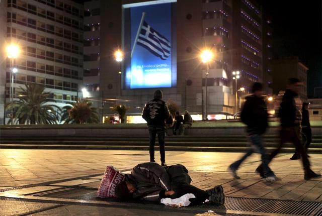 """Pobreza frente a un cartel que pone """"Grecia, te quiero""""."""