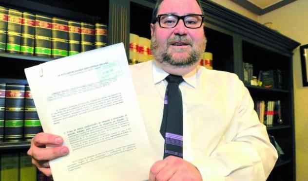 Andrés Miguel Oliván Lindo posa en su despacho con la demanda que ha presentado ante la Justicia.