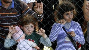 Niñas refugiadas esperando pasar la frontera
