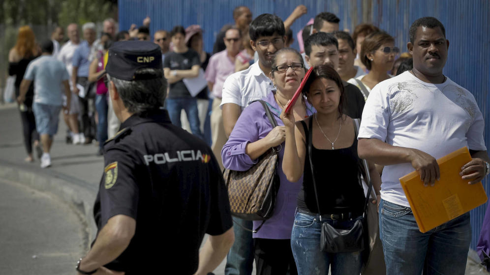 Inmigrantes hacen cola a la entrada de la Brigada Provincial de Extranjería y Fronteras del CIE de Aluche en Madrid