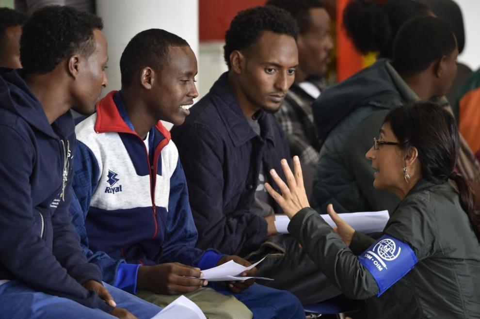 Un miembro de la Organización Internacional para las Migraciones (OIM) habla con un grupo de refugiados eritreos antes de viajar a Suecia.