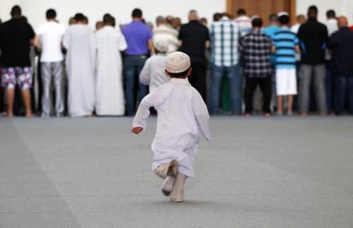 Dos niños corren hacia un grupo de fieles que rezan en la mezquita de Estrasburgo, Francia