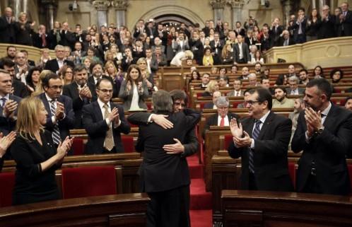 Artur Mas (de espaldas), saluda a Carles Puigdemont, poco antes de comenzar el pleno del Parlament.