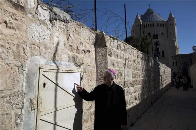 Un monje señala hoy un graffiti cerca de la Abadía de la Dormición, en la Ciudad Vieja de Jerusalén.