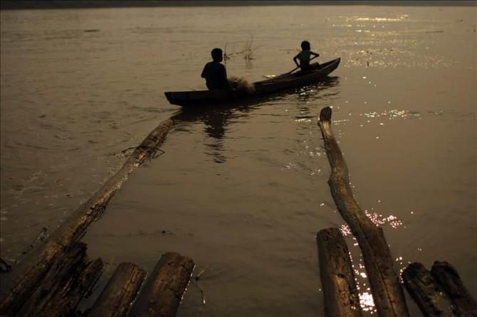 """Dos indígenas de la étnia Ticuna navegan en el río Amazonas, cerca del Parque Nacional Natural Amacayacu, conocido como el """"Río de las Hamacas"""", que ocupa gran parte del trapecio amazónico en el extremo sur del departamento del Amazonas (Colombia)."""