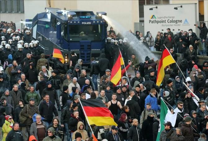 Un camión de la policia antidisturbios dispersa con chorros de agua una manifestación convocada en Colonia por el movimiento Pegida