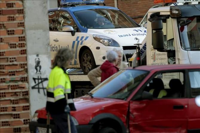 La grúa retira un coche policial que ha chocado contra otro vehículo al perseguir a dos hombres, uno de los cuales ha sido detenido, tras una agresión a un árbitro de un partido de fútbol de categoría benjamín, disputado en Salamanca, después de que los dos supuestos agresores huyeran por las calles del barrio de Los Pizarrales.