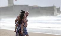 Varias personas disfrutan del primer baño del año en la playa de Carcavelos en Lisboa