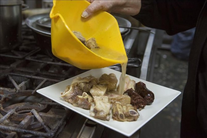 Elaboración en un restaurante de Granada de la olla de San Antón una plato típico de Andalucía Oriental con gran arraigo en la capital granadina que suma el beneplácito del santo para perdonar los excesos.
