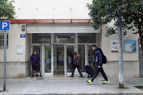 Dos pacientes en la entrada de un centro de salud de Valencia mientras un viandante pasa por la puerta.