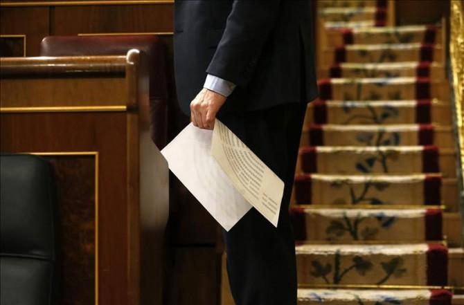 Un diputado sostiene un plano del nuevo hemiciclo en la sesión constitutiva del Congreso de los Diputados.