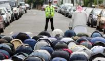 Un policía mira las plegarias de los musulmanes británicos en Londres