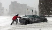 Un conductor empuja un coche en una calle de Queens, en Nueva York.