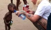 """Anja Ringgren Loven da una botella de agua a Esperanza, un niño de dos años expulsado de su casa por """"brujo"""". Llevaba 8 meses viviendo en la calle"""