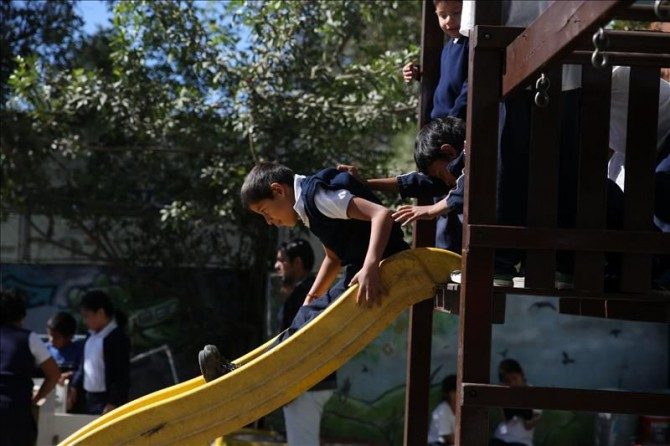 """Fotografía de un grupo de niños, mientras juegan en la sede de la asociación """"Guatemaltecos Extraordinarios"""" que ayuda a niños y jóvenes en riesgo de pandillas en la Ciudad de Guatemala (Guatemala)."""