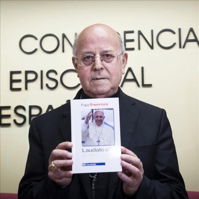 """El presidente de la Conferencia Episcopal Española (CEE), Ricardo Blázquez, muestra un ejemplar de la encíclica """"Laudato si"""" del papa Francisco."""