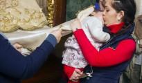 Una mujer pasa por el manto de la Virgen del Rocio a una niña para pedirle su protección, durante la presentación celebrada hoy en la aldea de El Rocío (Huelva).