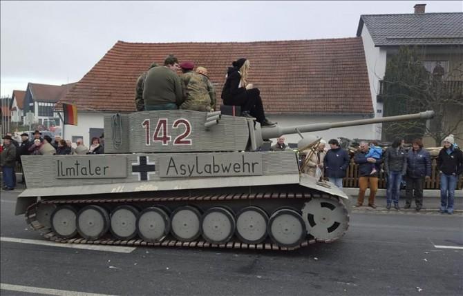 """Fotografía faciliada hoy, 8 de febrero de 2016 de una carroza que simula un tanque con una inscripción que reza """"Fuerza de Defensa de Asilo Ilmentaler"""" durante un desfile de carnaval en Reichtshausen, en le distrito bávaro de Pfaffenhofen (Alemania) ayer."""