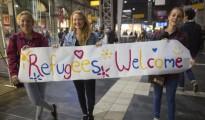 Tres jóvenes suecas muestran una pancarta dando la bienvenida a los refugiados