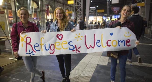 Tres jóvenes suecas muestran una pancarta muestra una pancarta dando la bienvenida a los refugiados