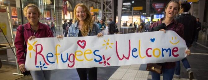 Tres jóvenes suecas portan una pancarta dando la bienvenida a los refugiados.