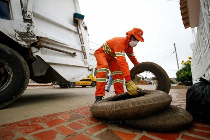 Un trabajador de la limpieza retira unos neumáticos para evitar que den cobijo al mosquito 'Aedes Aegypti', trasnmisor del zika, el 30 de enero de 2016 en Cucutá, Colombia