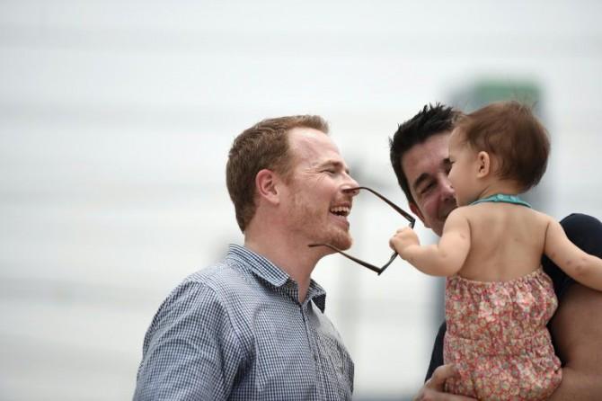 El estadounidense Gordon Lake (I) y el español Manuel Valero (D) juegan con Carmen, concebida por vientre de alquiler, tras una audiencia sobre su custodia en el Tribunal central de la familia en Bangkok, el 30 de marzo