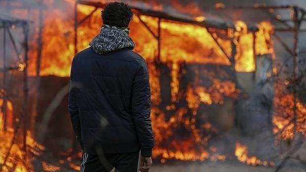 Un hombre observa un refugio en llamas durante el inicio del desmantelamiento del campamento de Calais