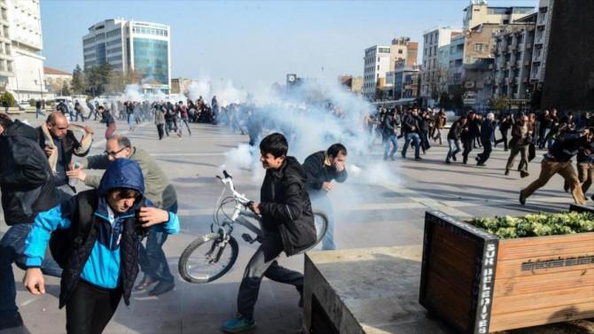 Manifestantes huyen de los efectos de los gases lacrimógenos disparados por la Policía turca en una protesta en la ciudad de Diyarbakir, contra el toque de queda impuesto por el Gobierno en las regiones kurdas, 14 de diciembre de 2015.
