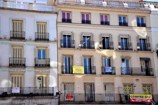 Fachada de un edificio de la capital en la que diferentes carteles de venta y alquiler de pisos.