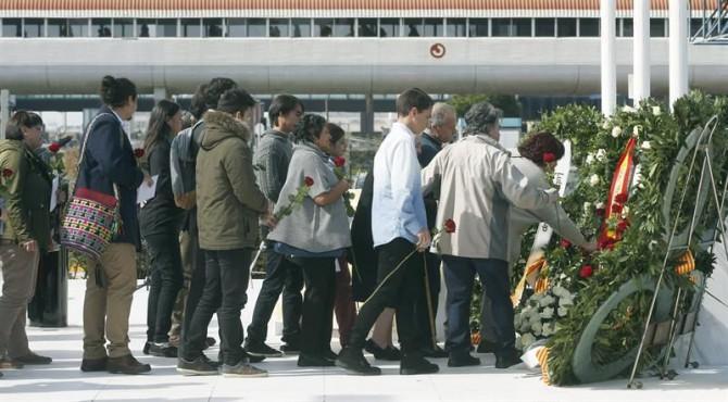 Varios familiares dejan rosas rojas en el monumento de recuerdo durante el acto de homenaje a las víctimas del accidente del vuelo Germanwings 9525, celebrado hoy en el aeropuerto de El Prat en la víspera del primer aniversario del siniestro.
