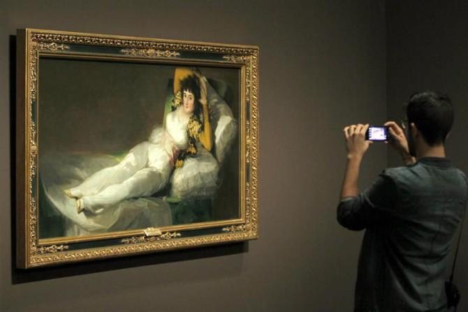 """Un joven fotografía """"La maja vestida"""" de Goya, expuesta en CaixaFórum Barcelona."""