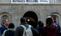 """Un cartel anuncia """"Bienvenidos Refugiados"""" desde la fachada del ayuntamiento de Barcelona, el 18 de marzo de 2016, días después de que la alcaldesa Ada Colau firmara un acuerdo de cooperación con sus homólogos de Lampedusa y Lesbos"""