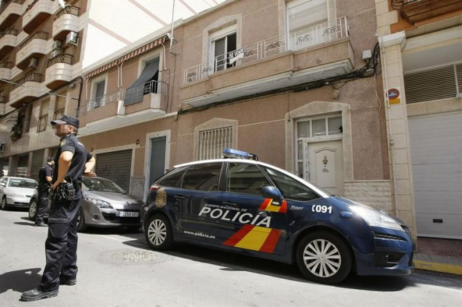 Un agente de la Policía Nacional junto a la fachada de una casa donde intentaron atracar.