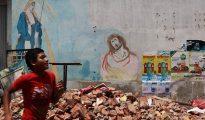 Un niño corre por una calle afectada por el terremoto, en Manta