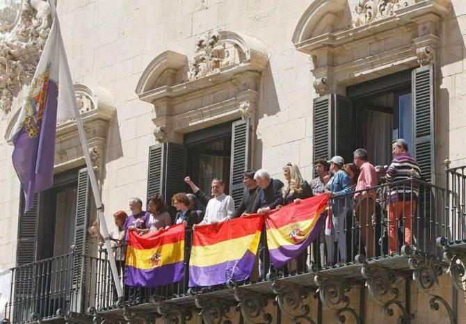 Concejales de Guanyar y simpatizantes con la República cuelgan banderas en el balcón del Ayuntamiento de Alicante conmemorando el 14 de abril.