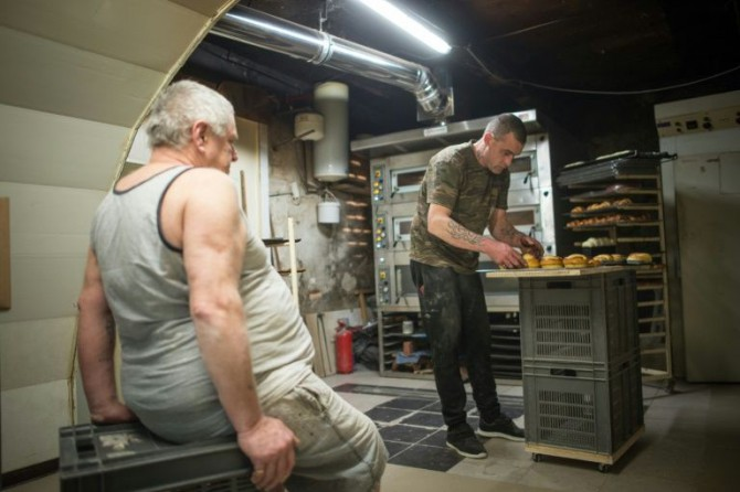 Michel Flamant (izq) y Jérôme trabajando en la panadería el 23 de marzo de 2016 en Dole, Francia
