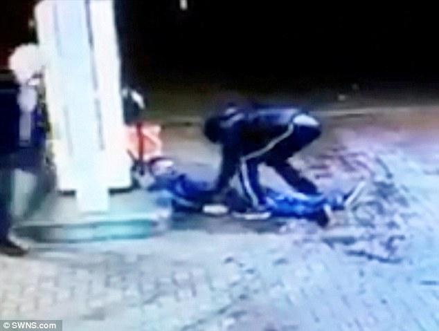 Uno de los criminales busca en los bolsillos de la víctima, que permanece inconsciente.