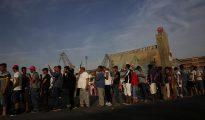 Refugiados esperan para recibir su cena en el campamento temporal del puerto del Pireo, cerca de Atenas, Grecia.